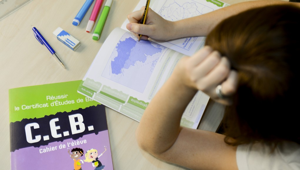 This picture shows a girl as she reads a Belgian Federation Wallonie-Bruxelles (Communaute Francaise de Belgique) Education Basic School exam book used to prepare the CEB (Certificat d'Etudes de Base) at the end of the sixth year primary school