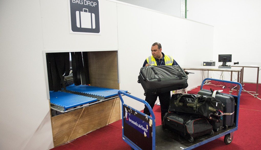 An airport worker handels luggage at the new temporary check-in site at Brussels Airport in Zaventem, Monday 04 April 2016. Since yesterday the airport has partially restarted. In the morning of Tuesday 22nd of March two bombs exploded in the departure hall of Brussels Airport and another one in the Maelbeek - Maalbeek subway station, which made around 35 deadly victims, not including the suicide bombers, and 340 injured people in total. ISIL (Islamic State of Iraq and the Levant - Daesh - ISIS) claimed responsibility for these attacks. BELGA PHOTO LAURIE DIEFFEMBACQ