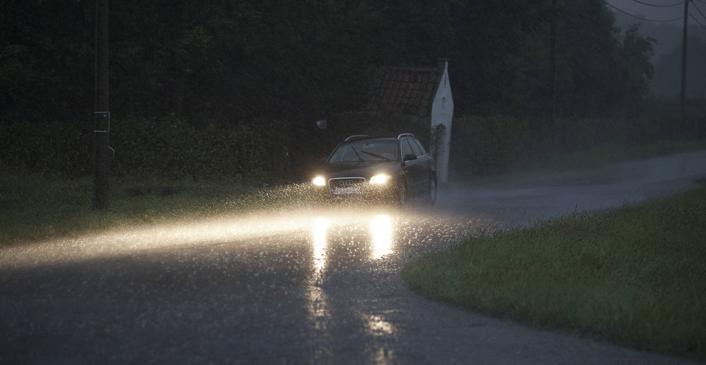 20150813 - KRUISHOUTEM, BELGIUM: Illustration picture shows a car driving with its lights under heavy rain falls on a small road on Thursday 13 August 2015, in Kruishoutem. After a very hot day, storms were announced all over Belgium. BELGA PHOTO NICOLAS MAETERLINCK