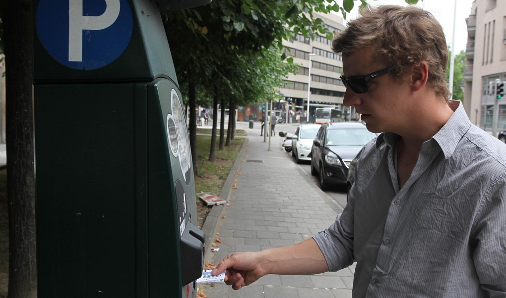 20110712 - BRUSSELS, BELGIUM: Illustration picture shows a man operating a Brussels parking meter, Tuesday 12 July 2011. During the Flemish holiday on July 11th, people were able to park for free due to a mistake in the machine programming. Both the Flemish holiday and the  holiday of the french-speaking community on September 27th are not supposed to be programmed as official holidays. BELGA PHOTO JULIEN WARNAND