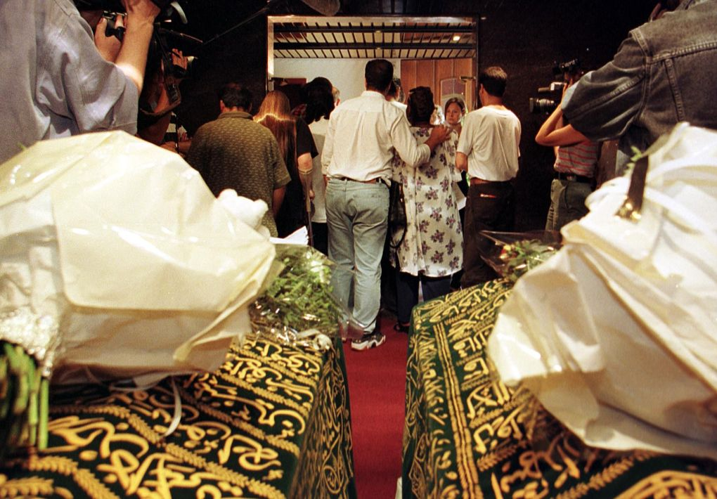"BRU20-06AUG99-ZAVENTEM,BEL: ""People without Papers"" from the beguinage church in Brussels representatives salute the coffins containing the mortal remains of Guinean students Yaguine KOITA and Fode TOUNKARA, who died on the landing gear of a Sabena plane, as stowaways coming from Guinee, here today in Zaventem. Belga Photo-Olivier MATTHYS/oma."