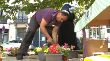 Des Anderlechtois remplissent des balconnières pour décorer le boulevard de la Révision